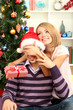 Young happy couple with presents sitting  near Christmas tree