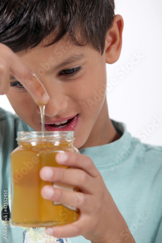 Little boy holding jar of honey