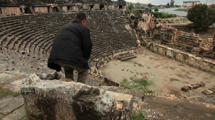 Tourist man visiting ancient  amphitheater