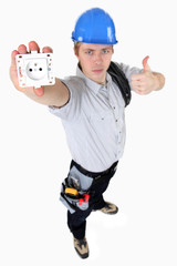 A young electrician showing an outlet.