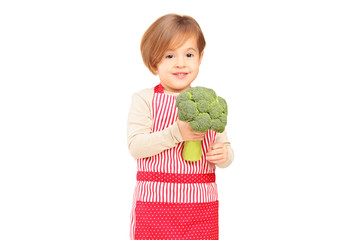 A smiling girl with apron holding a broccoli
