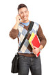 Smiling male student with bag and books talking on a phone