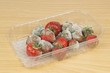 A packet of rotten mouldy strawberries on a table top