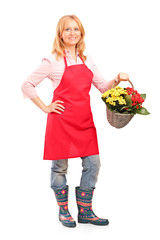 Mature florist holding a basket full of flowers