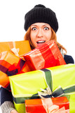 Ecstatic woman in winter hat with many gifts