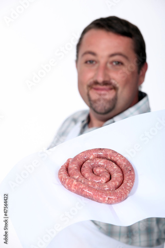 A butcher proudly presenting his sausages.