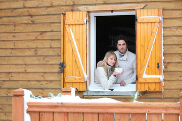 Couple looking out from chalet window