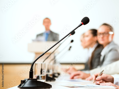 microphone stand in the row in front of businessmen