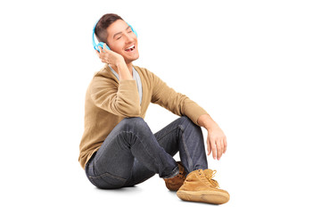 A young guy sitting on a floor and listening music on headphones