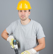 Young male construction worker working with screwdriver