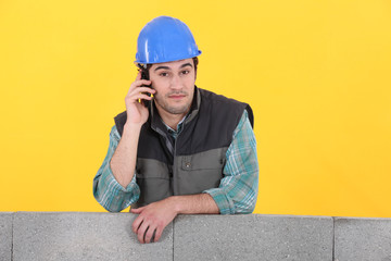 Builder stood by unfinished wall making telephone call