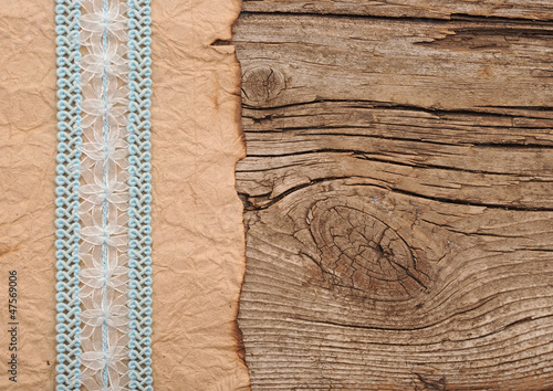 old paper with beutiful ribbon on brown wood texture
