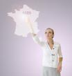 Femme appuyant sur une carte de France et touchant Paris