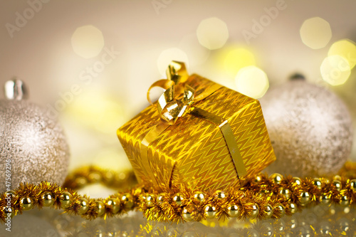 Christmas gift and baubles over shiny lights background