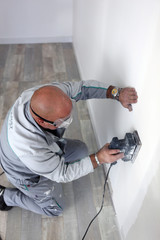 Man using power sander on wall