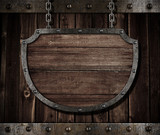 aged medieval shield signboard hanging on chains