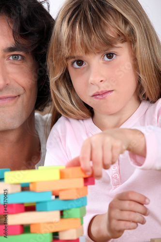 Father and daughter building a tower of blocks