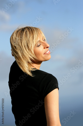 Blond woman stood outdoors on a sunny day