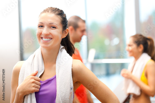 Woman in a fitness club. Towel around her neck