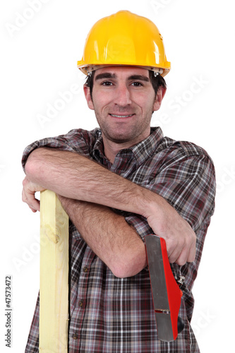 Tradesman holding a wooden plank and a plane
