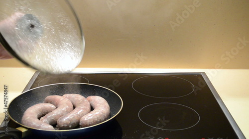 Fresh meat sausages baking in pan. Hand turns toasting meal