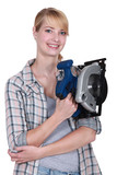 Smiling young woman holding circular saw