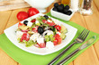 Fresh greek salad on plate on wooden table close-up