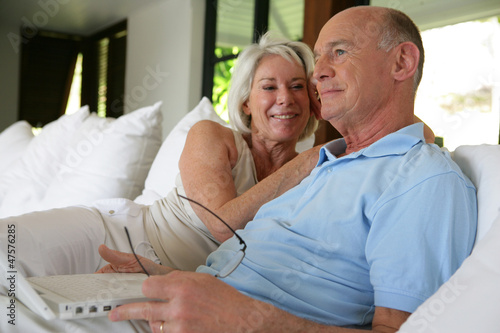 Couple sat on their veranda with laptop