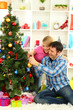 Young happy couple  decorates Christmas tree at home