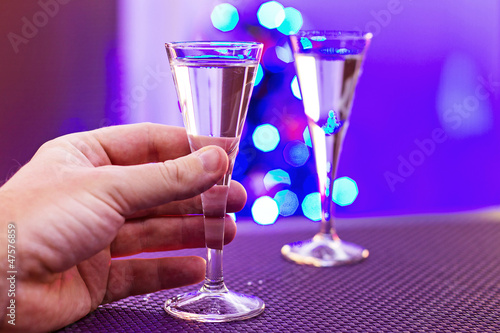 Hand taking glass of vodka at christmas time