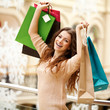 Happy young woman with shopping bags at mall