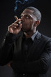 Black man wearing suit gangster style smoking cigar. Studio shot
