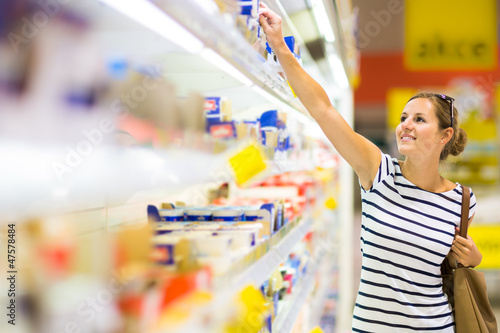 Beautiful young woman shopping for diary products at a grocery