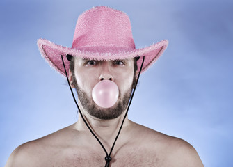 Cowboy in pink hat blowing a gumball.
