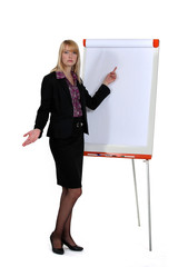 Businesswoman standing by a flip chart