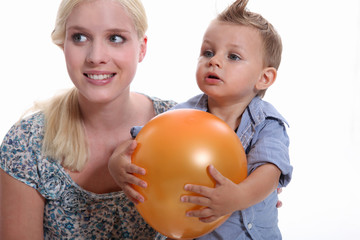 Mother and son holding a balloon.