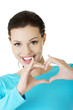 Attractiveyoung woman showing heart gesture