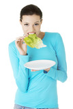 Fit young beautiful woman eating salat