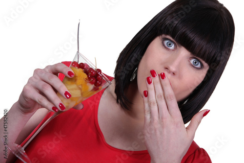 Surprised woman eating fruit salad