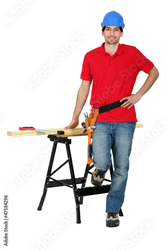 Man with wood, a workbench and saw