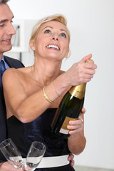 couple opening a bottle of champagne