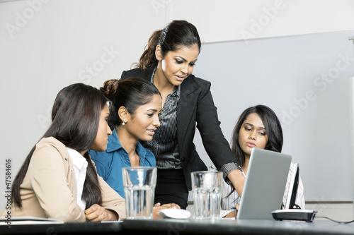 Indian colleagues working around a laptop