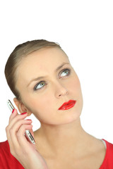 Blonde woman in red listening to a mobile phone