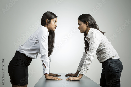 Angry Indian business women staring at each other.