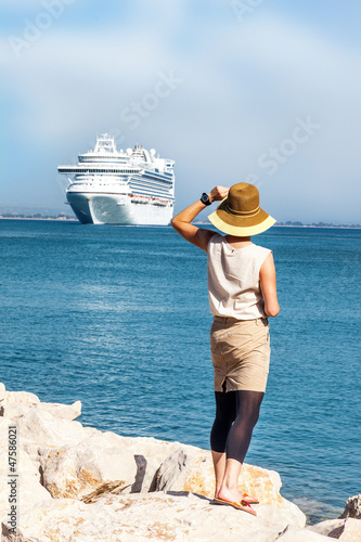 Woman with hat standing at sea