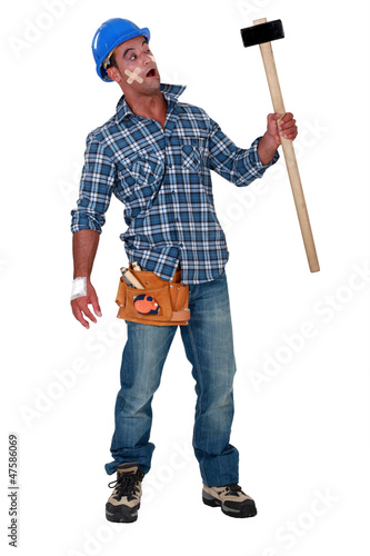 Injured workman with mallet in hand
