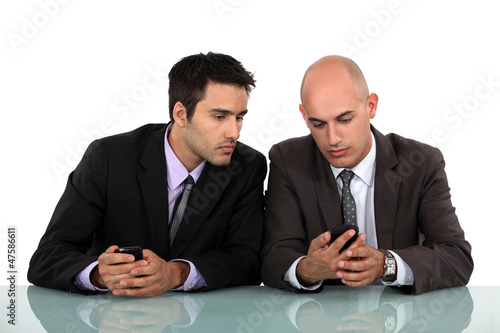 Businessmen comparing phones