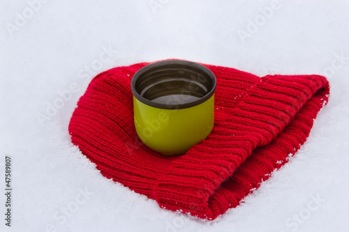 Red wool hat and green thermos mug