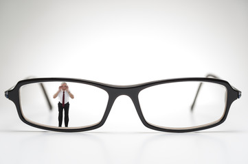 Diminutive elderly man peering through spectacles