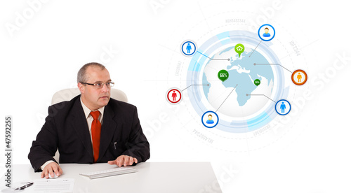 businessman sitting at desk and typing on keyboard with globe an